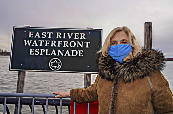 "Rep. Malone poses near a sign which says ""East River Waterfront Esplanade"". She is wearing a brown heavy coat and blue face mask."